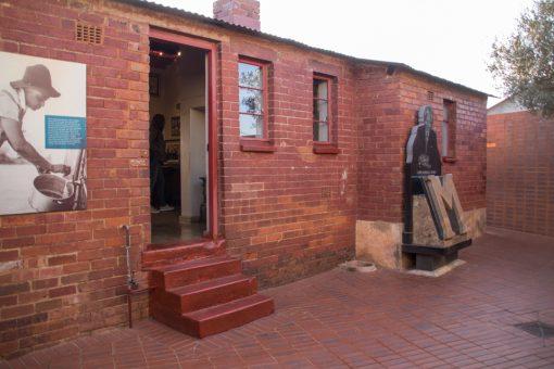 Entrada da casa de Mandela que é toda revestida por tijolos avermelhados.