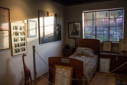Cama de solteiro na casa de mandela. O quarto tem quadros na parede com fotos.
