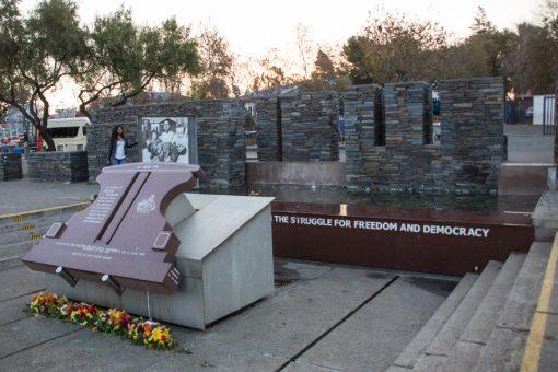 Memorial com parede de pedras, um espelho d'água e a foto de Hector Pieterson sendo carregado.